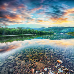 Fotobehang Rivier Mountain river stream of water in the rocks with majestic sunset sky.