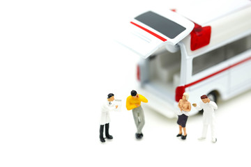 Miniature people : Doctor and Paramedic attending to patient in ambulance,Medicine ambulance concept