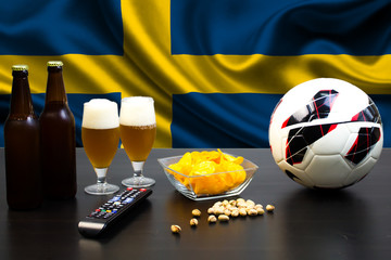 2 bottles of beer, 2 glasses of beer next to the football on the background of the flag of Sweden.