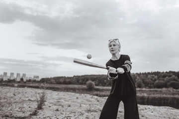 black and white photo of woman playing with baseball bat and ball at cloudy day