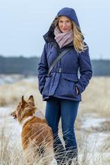 Schöne Frau macht mit Ihrem Hund einen Spaziergang am Strand
