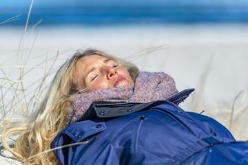 Schöne Frau liegt in der Sonne auf einer Düne und schläft