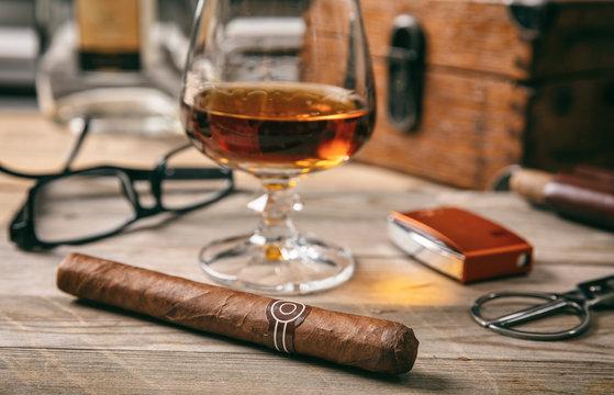Cuban cigar closeup on wooden desk, blur glass of brandy