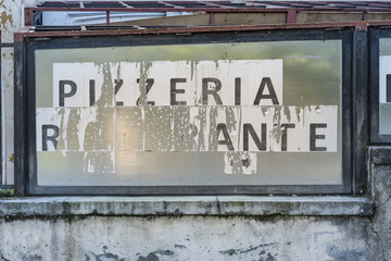 Rundown and weathered Italian pizzeria and restaurant sign on an old wall