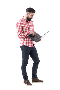Bearded modern millennial hipster business man working and using laptop computer. Full length isolated on white background.
