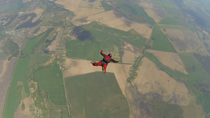 Skydiver in a red jumpsuit freefalling in classical position