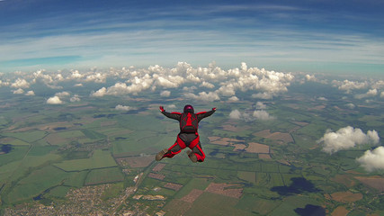 Photo sur Toile Aerien Skydiver in a red jumpsuit freefalling above the clouds