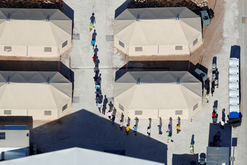 "Immigrant children, many of whom have been separated from their parents under a new ""zero tolerance"" policy by the Trump administration, are shown walking in single file between tents in their compound next to the Mexican border in Tornillo, Texas"