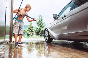Boy helps to wash a car