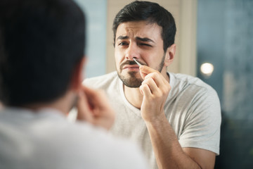 Handsome Man Trimming Nose Hair In Bathroom