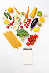 Photo of apples, oranges, pasta, broccoli, avocado, carrots, clean notebook