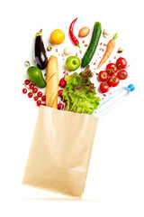 Photo of paper bag with vegetables, fruit, loaf and bottle of water