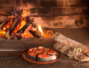 Steaks of fresh salmon near burning firewood