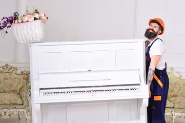 Loader moves piano instrument. Man with beard, worker in overalls and helmet lifts up piano, white background. Delivery service concept. Courier delivers furniture in case of move out, relocation.