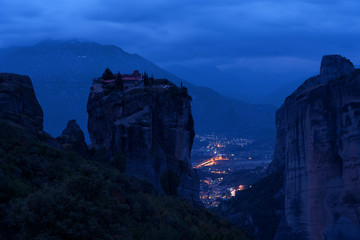 Magnificent nightscape. Monastery Holy Trinity, Meteora, Greece. UNESCO world heritage Site. Epic landscape with temple at the edge of cliff at dramatic sky background.