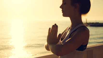 Young woman practicing yoga outdoors by the sea at sunset. Girl standing with eyes closed and prayer hands. Female portrait in profile.
