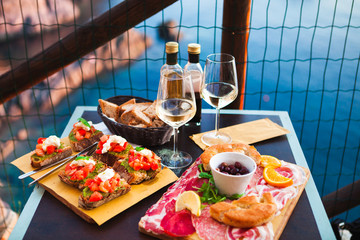 Romantic dinner for two at sunset. White wine and Tasty italian snack: fresh bruschettes  and meat on the board in outdoor cafe with amazing view in Manarola