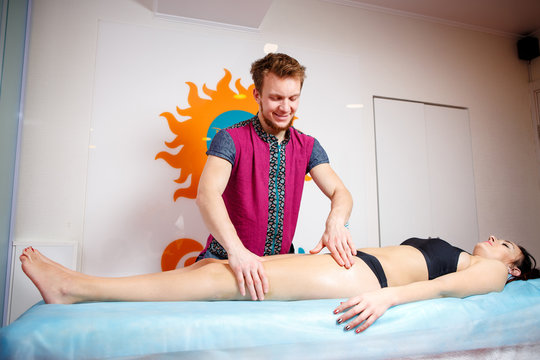 The concept of massage and health. A male massage therapist does lymphatic drainage and massage for toning the muscles of a girl in black underwear on a table in a physiological room.