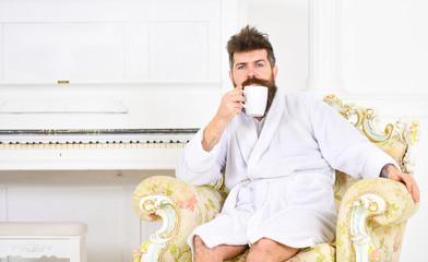 Guy in white bathrobe enjoying morning coffee. Thoughtful man sitting in armchair. Sleepy fellow drinking coffee or tea at home