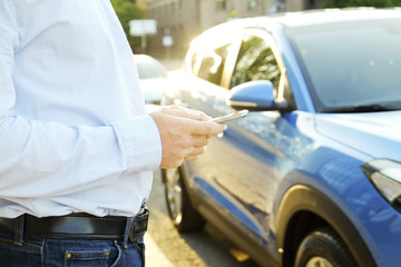 Young man in blue shirt formal ware standing near his new caribbean blue car, using smartphone. Male holding blank screen cell phone in hands. Gps navigation concept. Close up, copy space, background.