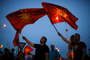 Supporters of opposition party VMRO-DPMNE wave Macedonian flags as they take part in a protest over compromise solution in Macedonia's dispute with Greece over the country's name in Skopje