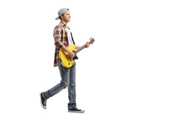 Teenage boy walking and playing an electric guitar