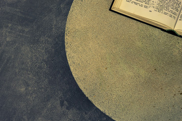 Open Holy Bible on a stone round table. Beautiful dark  background. Religious concept.
