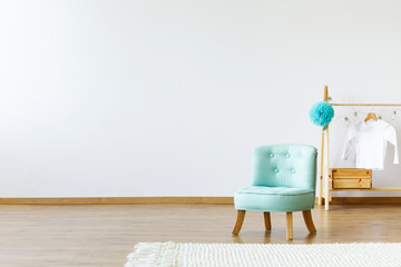 Mint chair, wooden hanger with a T-shirt on pompom and rug on an empty wall. Place your product