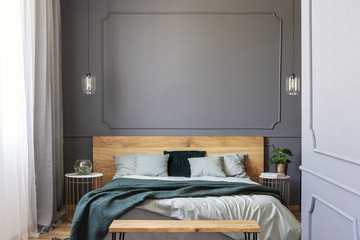 Green blanket on wooden bed with pillows in grey bedroom interior with wall with molding. Real photo