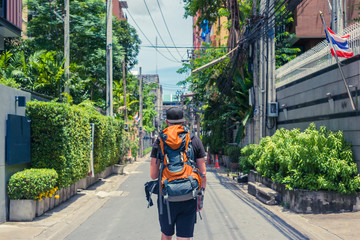 Man with backpack walking in the streets of Bangkok. Backpacker in Thailand, Asia Wall mural