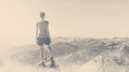 Fotomurales - Vintage toned image of woman on a mountain summit