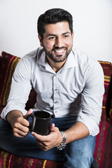 Smiling man sit on sofa and drink cup of coffee