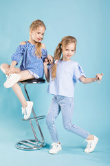 Girls twins in light blue clothes are posing near a bar stool on a blue background.