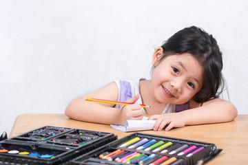 Cute Little Thai Girls enjoy drawing art.