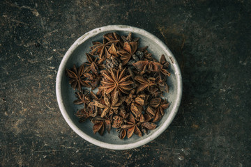 Star anise in a bowl with rustic background