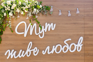 Decorated photozone with inscription on cyrylic letters HERE LIVES A LOVE