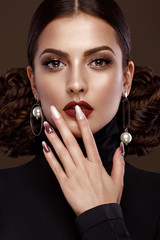 Pretty girl with unusual hairstyle, bright makeup, red lips and manicure design. Beauty face. Art nails. Studio portrait