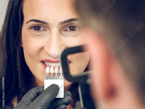 Dentist picking color of denture
