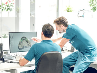 Dentists modeling jaw on computer