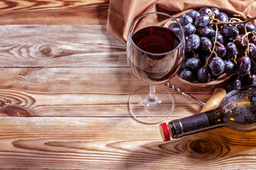 Red wine. Red wine in a glass, red grapes and dusty bottle on a wooden background. Copy space