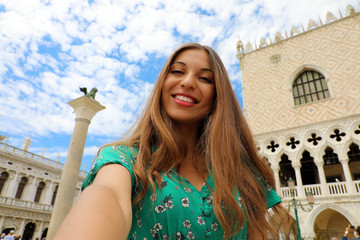 Happy beautiful woman taking selfie photo in Venice with white clouds in the sky. Tourist girl smiling at camera in St. Mark square in Venice, Italy.