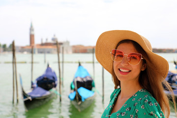 Smiling woman with sunglasses and hat looking at camera with Venice Lagoon on the background