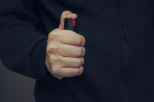 A man's hand holding a small bottle of pepper spray