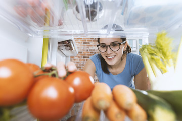 Woman taking healthy food from the fridge