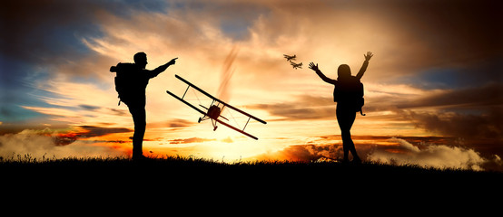 couple looks at old biplanes fly at sunset