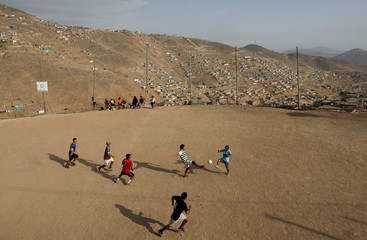 Men play soccer at a makeshift soccer pitch in Nueva Union shantytown in Villa Maria del Triunfo district of Lima