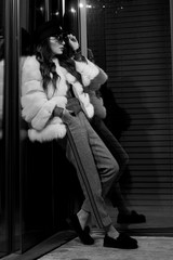 Full body portrait of fashionable young long haired brunette woman wearing large round sunglasses, cap, luxurious white fur coat, standing with her back leaning on large glass window and posing.