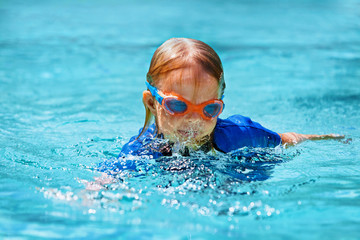 Happy child in wetsuit and goggles learn to swim, have fun in outdoor pool. Healthy family lifestyle, little kids water sports activity, swimming lessons with parents at training aqua classes.
