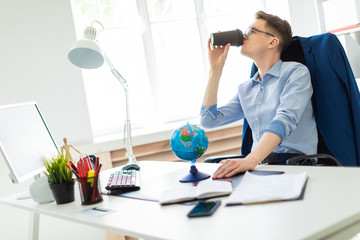 A young man sits in the office at a computer desk, holds a globe with his hand and drinks coffee.