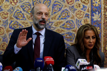 Jordan's Prime Minister Omar al-Razzaz and Minister of State for Media Affairs Jumana Ghunaimat arrive for their news conference in Amman